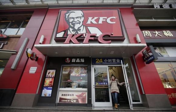 A woman walks out from a KFC restaurant as she speaks on her mobile phone in Wuhan