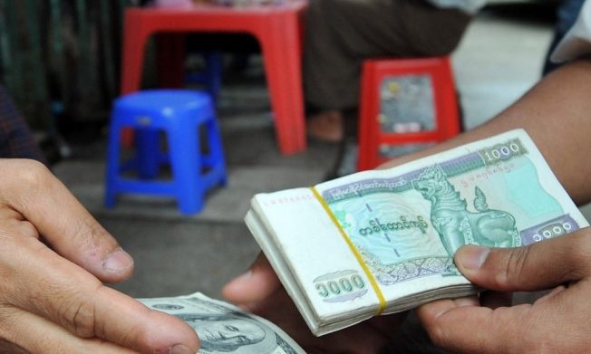 Money changers exchanging Myanmar kyat bank notes into US dollars in a back alley of the country's main city and former capital Yangon. Photo: AFP / Soe Than Win