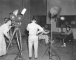 Iva Toguri reenacts her wartime radio broadcasts for an Army signal corps film crew.